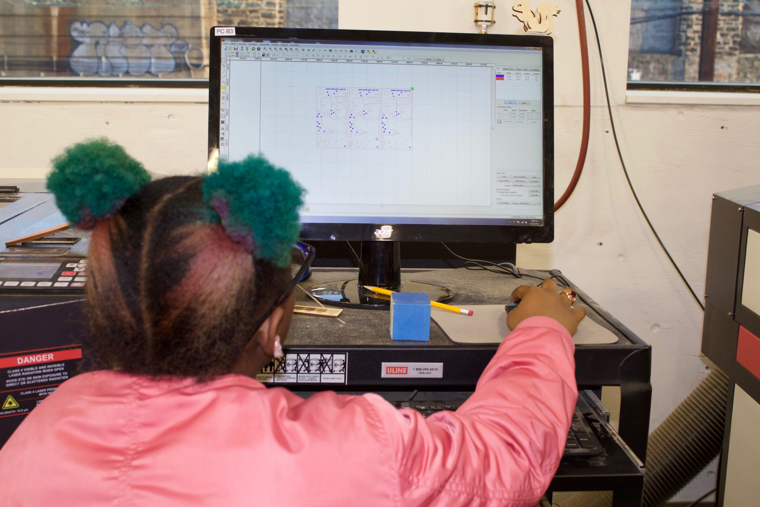 Young girl working at computer with digital fabrication software.